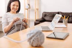 Pozytywny azjatykci kobiety dzianie w biurze Fotografia Stock