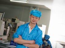 Pozytywny azjatykci mężczyzna pracownika pobyt przed pracującym miejscem zdjęcie royalty free