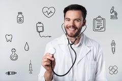 Pozytywny brodaty doktorski uśmiechać się jego stetoskop i trzymać obraz stock