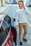Pozytywny dobry przyglądający mężczyzna trzyma samochodowego drzwi Zdjęcia Royalty Free
