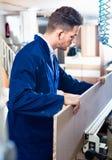 Pozytywny faceta naprawiania chipboard na stole przy warsztatem Obrazy Stock