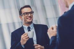 Pozytywny mądrze biznesmen pije kawę zdjęcia stock