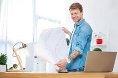 Pozytywny mądrze pracownik ono uśmiecha się podczas gdy patrzejący laptop obraz stock