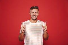 Pozytywny mężczyzna gestykuluje palce wskazujących oddolny a w pasiastej koszulce zdjęcia royalty free