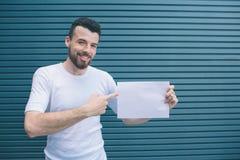 Pozytywny mężczyzna jest stojący białego kawałek papieru w lewej ręce, trzymający i wskazujący z palcem na dobrze jeden Facet jes fotografia royalty free