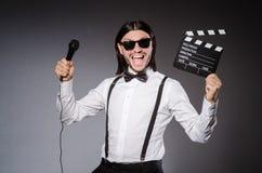 Pozytywny mężczyzna mienia clapperboard i mikrofon Obraz Stock