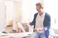 Pozytywny mężczyzna pracuje z papierami w biurze Fotografia Royalty Free