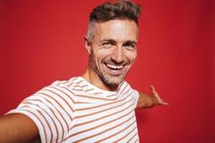 Pozytywny mężczyzna uśmiecha się selfie fotografię i bierze w pasiastej koszulce, zdjęcia stock