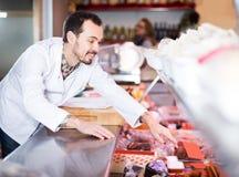 Pozytywny męski sklepowy asystent demonstruje kiełbasy w masarce Obraz Royalty Free