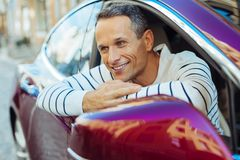 Pozytywny przystojny mężczyzna patrzeje z jego samochodowego okno Zdjęcia Stock