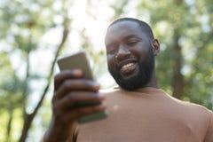 Pozytywny radosny mężczyzna używa jego nowożytnego smartphone obraz stock