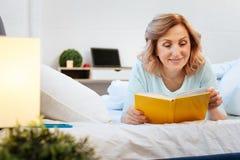 Pozytywny uśmiechnięty kobiety lying on the beach na jej łóżka i czytania hardcover książce zdjęcie stock