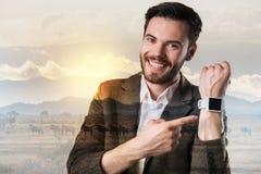 Pozytywny uśmiechnięty mężczyzna demonstruje jego nowożytnego mądrze zegarek zdjęcia royalty free