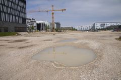 Pozza del cantiere con le costruzioni e gru nei precedenti fotografie stock