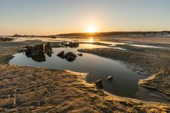Pozza di marea a distanza su una spiaggia sudafricana fotografia stock libera da diritti