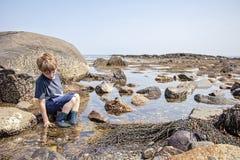 Pozze di marea d'esplorazione del ragazzo sulla costa di New Hampshire fotografia stock