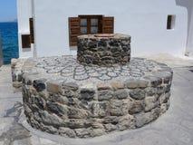 Pozzo antico antico da una pietra con una copertura fotografia stock