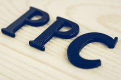 PPC (или оплата в щелчок) подписывают на деревянной предпосылке - винтажном тоне Стоковое фото RF