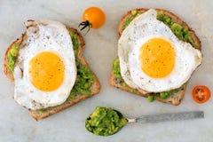 Öppen avokado, äggsmörgåsar på marmor Arkivfoto