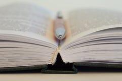 ?ppen bok En penna ligger mellan sidorna i en ?ppen bok royaltyfri foto