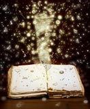 Öppen bok med magiska ljus- och magibokstäver Arkivfoton