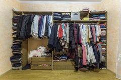 ?ppen kl? hemlig garderob mycket av den olika mannen och kvinnlig f?rgrik kl?der och tillbeh?r p? h?ngare och hylla modernt royaltyfri fotografi