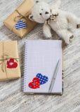 Öppen ren Notepad, hemlagade valentin daggåvor i kraft papper, pappers- hjärtor, leksakbjörn på den vita trätabellen Arkivbild