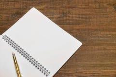 Öppen spiral - destinerad anteckningsbok med vita sidor och den guld- pennan Arkivfoto