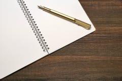 Öppen spiral - destinerad anteckningsbok med vita sidor och den guld- pennan Royaltyfri Bild