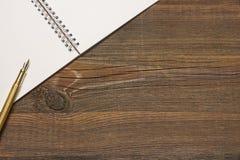 Öppen spiral - destinerad anteckningsbok med vita sidor och den guld- pennan Arkivbilder