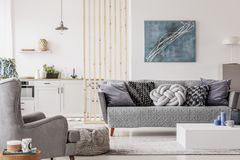 ?ppen studiol?genhet med liten vit k?k och vardagsrum med den gr?a soffan och tr?kaffetabellen arkivbild