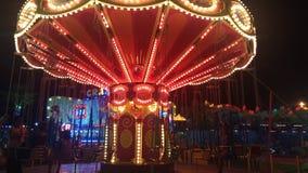 Ppeople vilar i nöjesfält och rider karusell royaltyfri bild