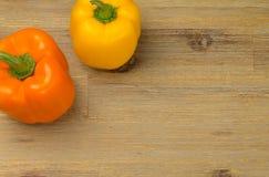 Ppers Paprika der orange und gelben Glocke auf dem Holztischhintergrund Stockbild