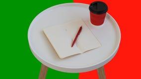?ppet tomt tomt anm?rkningspapper med den r?da pennan, den r?da pappkoppen kaffe som g?r p? den vita runda tidskriftstr?tabellen, royaltyfri fotografi
