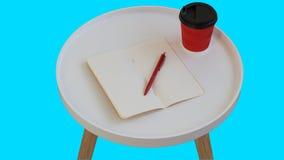 ?ppet tomt tomt anm?rkningspapper med den r?da pennan, den r?da pappkoppen kaffe som g?r p? den vita runda tidskriftstr?tabellen, arkivfoton