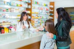 Ppharmacist που δίνει τις βιταμίνες στο κορίτσι παιδιών στο φαρμακείο φαρμακείων στοκ φωτογραφία