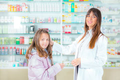 Ppharmacist giving vitamins to child girl in pharmacy drugstore Royalty Free Stock Image