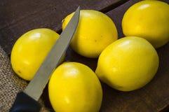 PPhotos de citron avec le couteau sur les planchers en bois, moitié d'un citron de main-coupe, divisant un citron en deux parts é Photographie stock