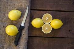 PPhotos de citron avec le couteau sur les planchers en bois, moitié d'un citron de main-coupe, divisant un citron en deux parts é Photo stock