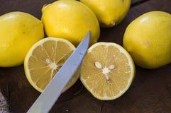 PPhotos de citron avec le couteau sur les planchers en bois, moitié d'un citron de main-coupe, divisant un citron en deux parts é Image libre de droits