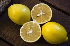 PPhotos de citron avec le couteau sur les planchers en bois, moitié d'un citron de main-coupe, divisant un citron en deux parts é Images stock