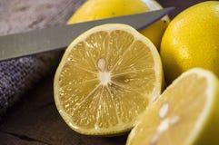 PPhotos de citron avec le couteau sur les planchers en bois, moitié d'un citron de main-coupe, divisant un citron en deux parts é Photos stock