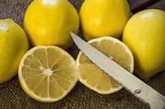 PPhotos de citron avec le couteau sur les planchers en bois, moitié d'un citron de main-coupe, divisant un citron en deux parts é Photo libre de droits