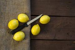 PPhotos do limão com a faca em assoalhos de madeira, metade de um limão do mão-corte, dividindo um limão em duas porções iguais,  Fotos de Stock