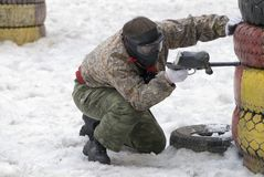 Pplayer in paintball. The player paintball in an ambush in the winter Royalty Free Stock Photo