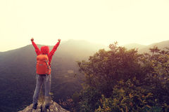 Öppna armar för kvinnafotvandrare på klippan för bergmaximum Royaltyfri Bild