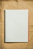 Öppna den tomma anmärkningsboken på inpackningspapper Arkivfoto