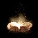 Öppna händer med glödande lampor Arkivbild
