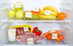 Öppna kylen mycket av frukter, grönsaker och meat Arkivbild