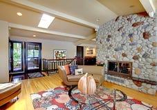 Öppna modernt lyxigt hemmiljövardagsrum och stena spisen. Fotografering för Bildbyråer